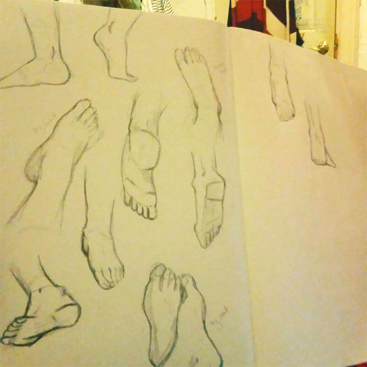 Quick sketches of feet inside practice sketchbook